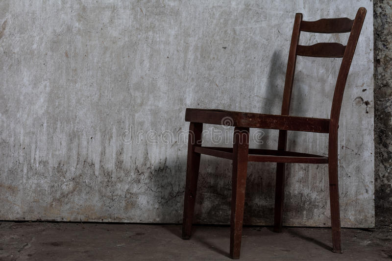 与镇压的老被佩带的椅子在被放弃的一个水泥地板上 图库摄影