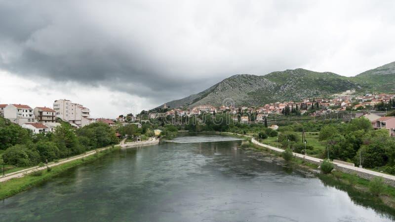 与镇的美丽如画的风景河岸的 波黑,塞族共和国 Trebisnjica河和特雷比涅看法  库存照片