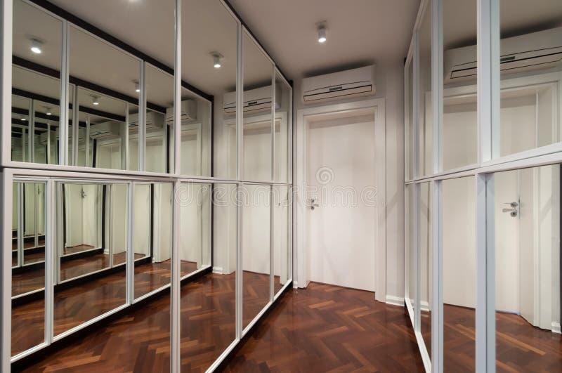 与镜子衣橱门的现代走廊内部 免版税库存图片