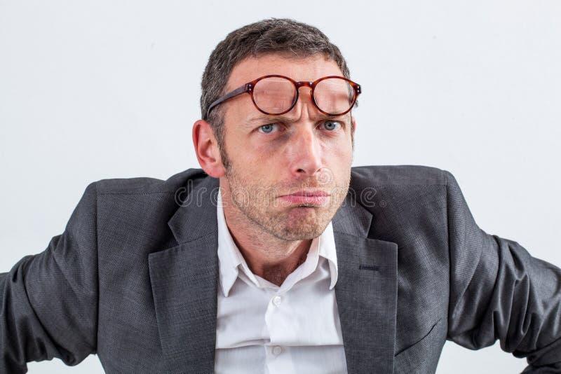 与镜片的不快乐的商人在他的怀疑的前额 库存图片