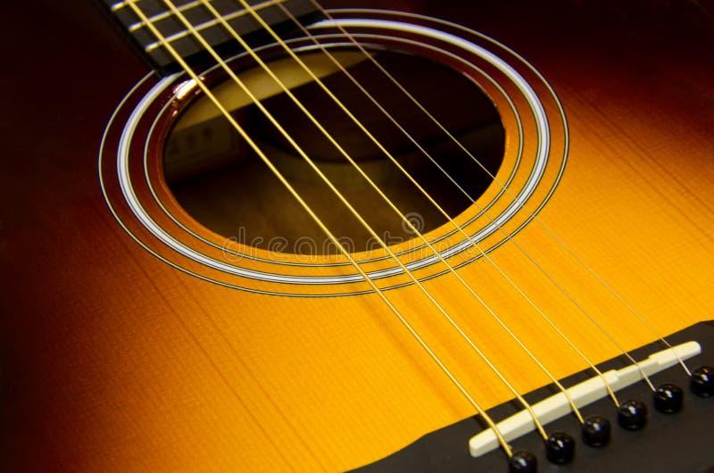 与镶有钻石的旭日形首饰的结束的声学吉他特写镜头 免版税库存图片