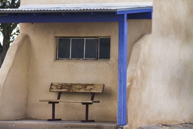 与长凳、窗口和蓝色修剪的Adobe避难所在营地 库存照片
