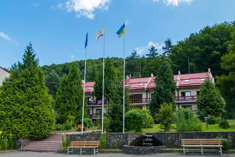 与长凳的美好的两层旅馆复合体和一个喷泉在以绿色树为背景的庭院里 库存照片