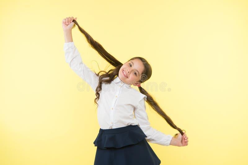 与长发发型的成交单独 孩子女孩长的马尾辫发型 儿童校服做发型 孩子 库存图片