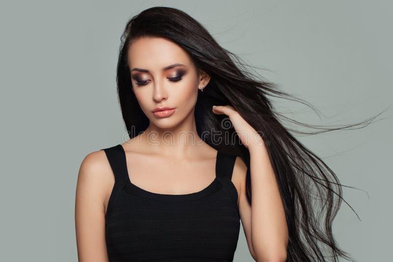 与长的健康发型的俏丽的妇女时装模特儿 免版税库存图片