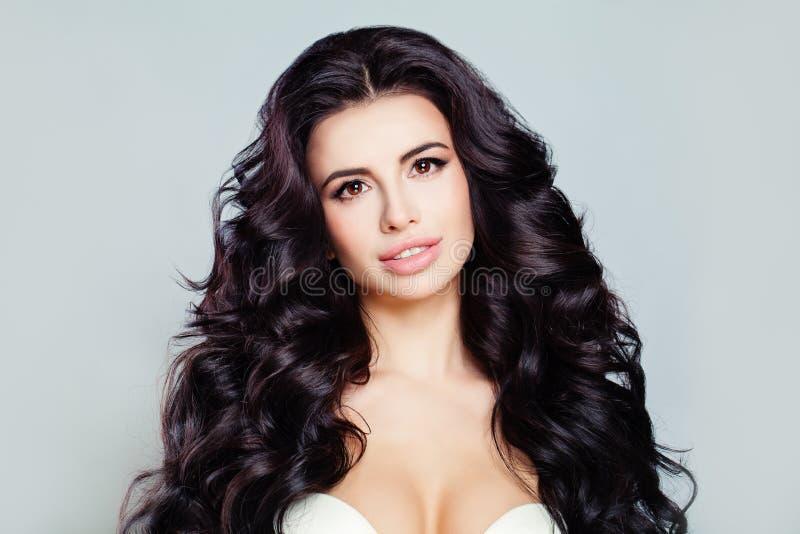 与长的发光的波浪发和完善的皮肤的美好的妇女模型 与卷曲发型的俏丽的模型 免版税库存照片