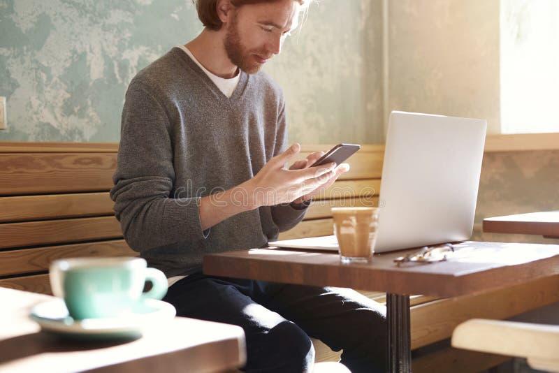 与长的头发佩带的毛线衣的英俊的商人叫由坐在晴朗的咖啡馆的智能手机,使用食用的膝上型计算机单独咖啡 免版税库存图片