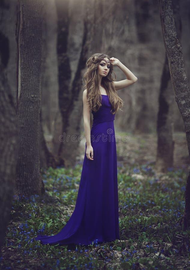 与长的头发和蓝眼睛的有火车的一件长的蓝色礼服走通过春天开花的女孩矮子在冠状头饰和 免版税库存照片