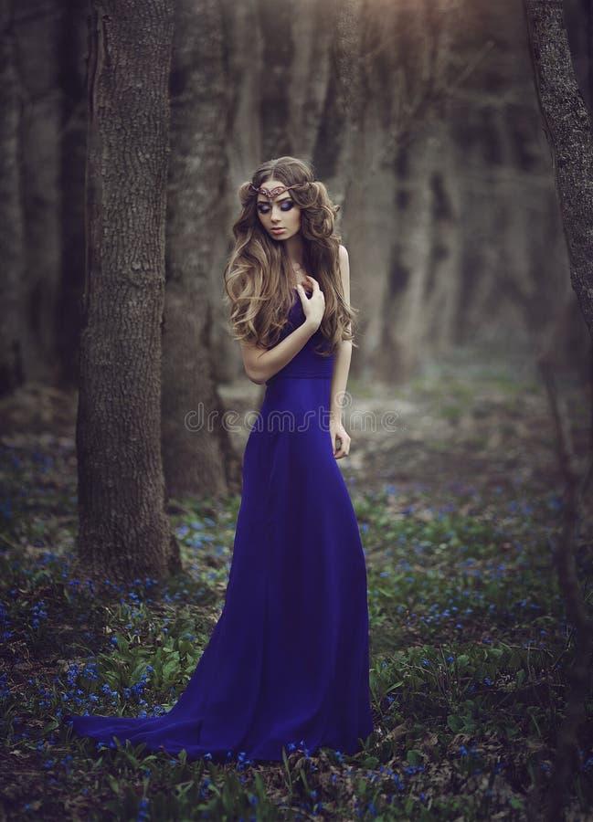 与长的头发和蓝眼睛的有火车的一件长的蓝色礼服走通过春天开花的女孩矮子在冠状头饰和 免版税库存图片