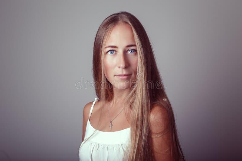 与长的头发和蓝眼睛的白种人白肤金发的年轻美好的女孩妇女模型在白色礼服 免版税库存照片