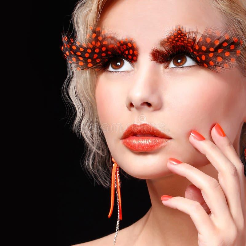 与长的橙色睫毛的时尚白肤金发的模型。专业构成为万圣夜 免版税库存图片