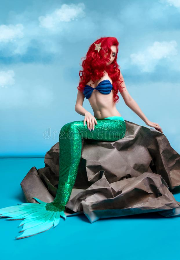 与长的红色头发的美人鱼坐石头 图库摄影