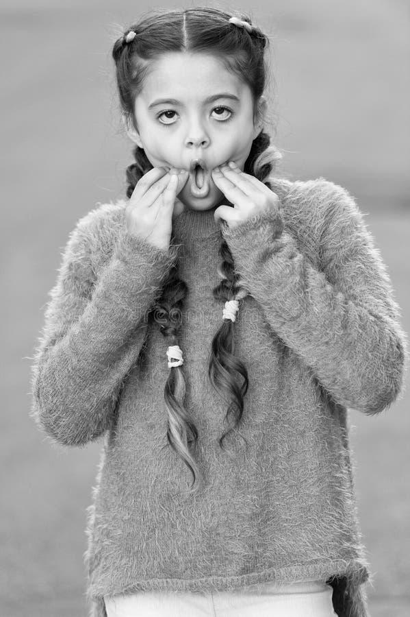与长的结辨的头发的孩子做乏味鬼脸面孔 因此不耐烦 变乏味的女孩疯狂 与表情的戏剧 图库摄影