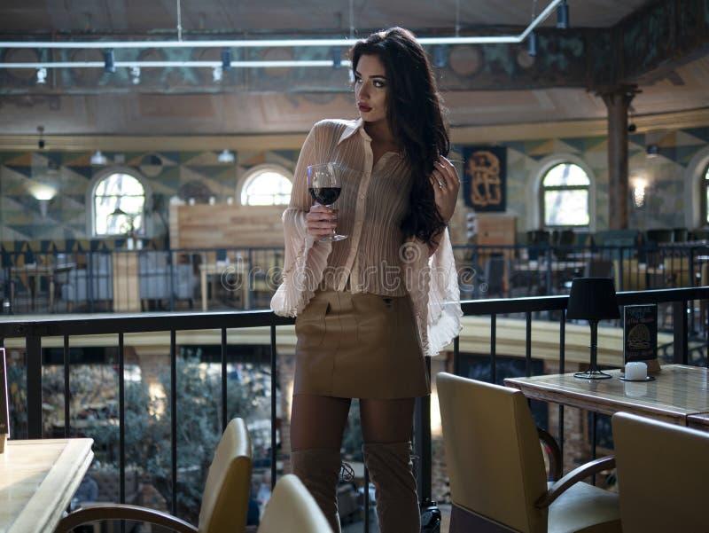 与长的腿的美女模型在一条短裙站立与一块玻璃在餐馆 库存照片