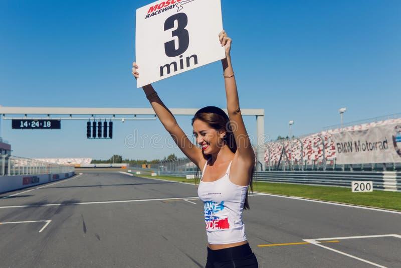 与长的头发和一件白色T恤杉的女孩模型在种族车手前带有标志在轨道的时间 免版税库存照片
