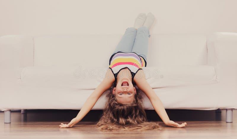 与长的头发的小女孩孩子颠倒在沙发 库存照片