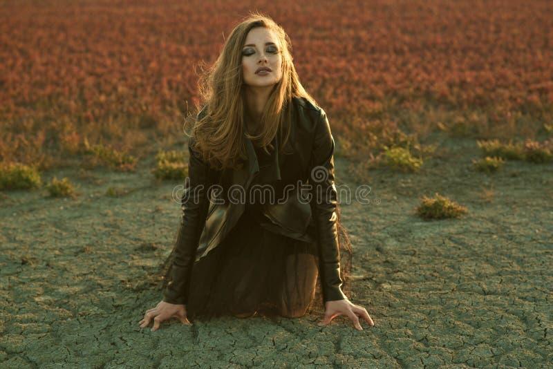 与长的头发的年轻迷人的模型在黑遮掩的礼服和时髦的皮夹克坐与闭合的眼睛的地面 库存图片
