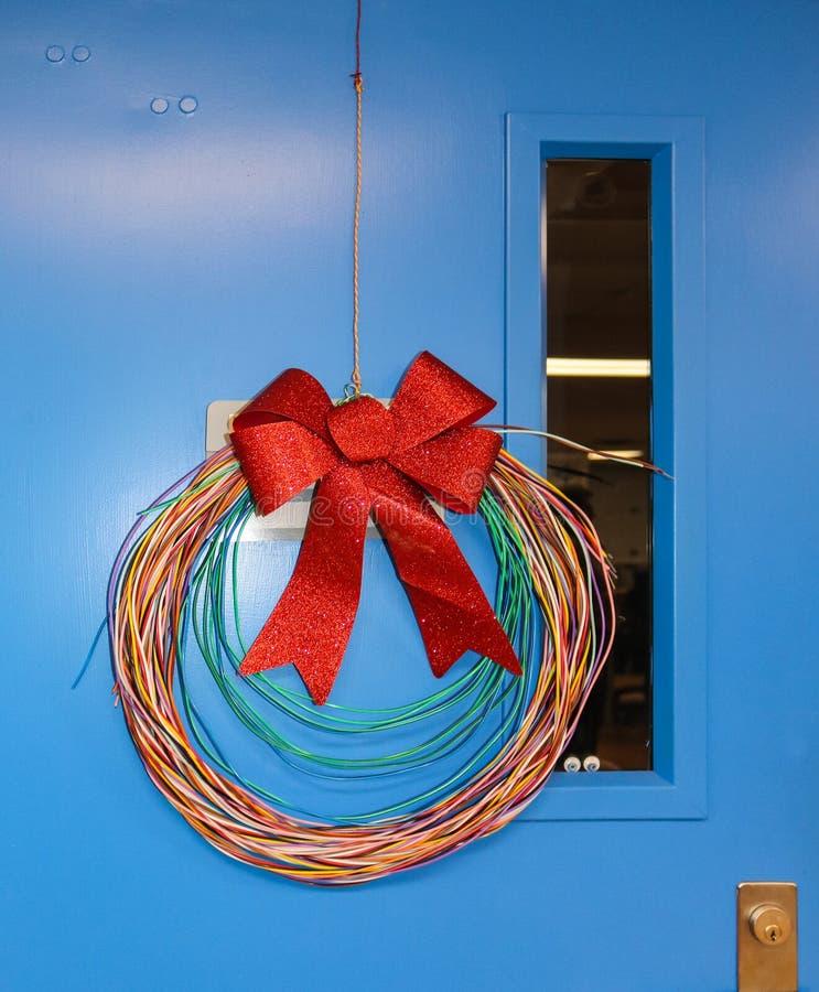 与闪光弓的网络缚住的圣诞节花圈在蓝色门垂悬了 库存图片