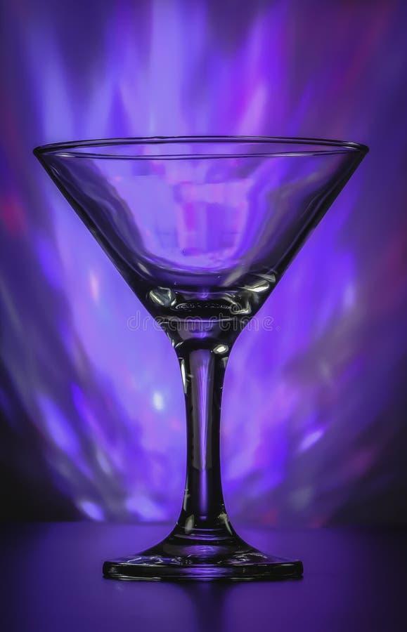与闪动的明亮的紫罗兰色光的马蒂尼鸡尾酒玻璃在背景 图库摄影