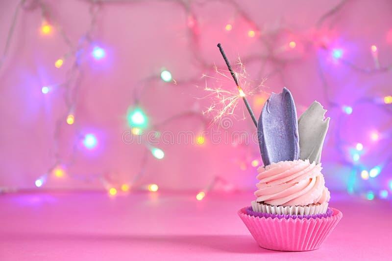 与闪烁发光物的可口生日杯形蛋糕反对被弄脏的光 免版税图库摄影