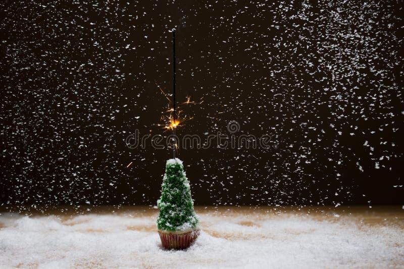 与闪烁发光物的圣诞树在雪背景  免版税库存照片