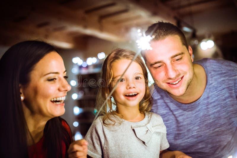 与闪烁发光物的年轻家庭在圣诞节时间在家 库存图片