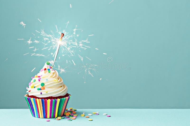 与闪烁发光物的庆祝杯形蛋糕 免版税库存照片