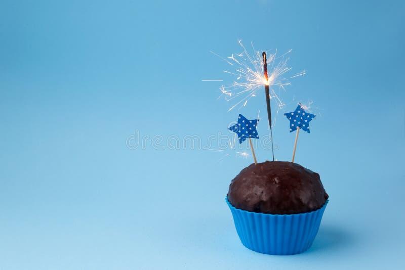 与闪烁发光物的杯形蛋糕反对蓝色背景 免版税库存图片