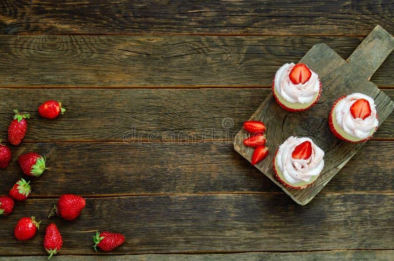 与闪烁发光物的杯形蛋糕在木背景的桌上 免版税库存照片