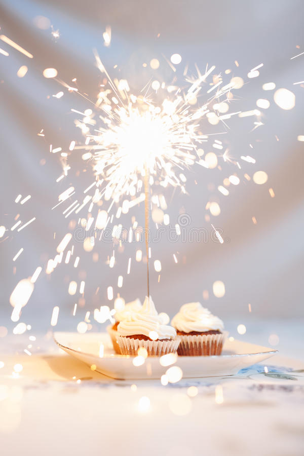 与闪烁发光物的生日杯形蛋糕 库存照片