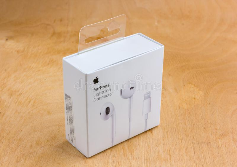 与闪电连接器的苹果计算机EarPods在箱子 库存照片