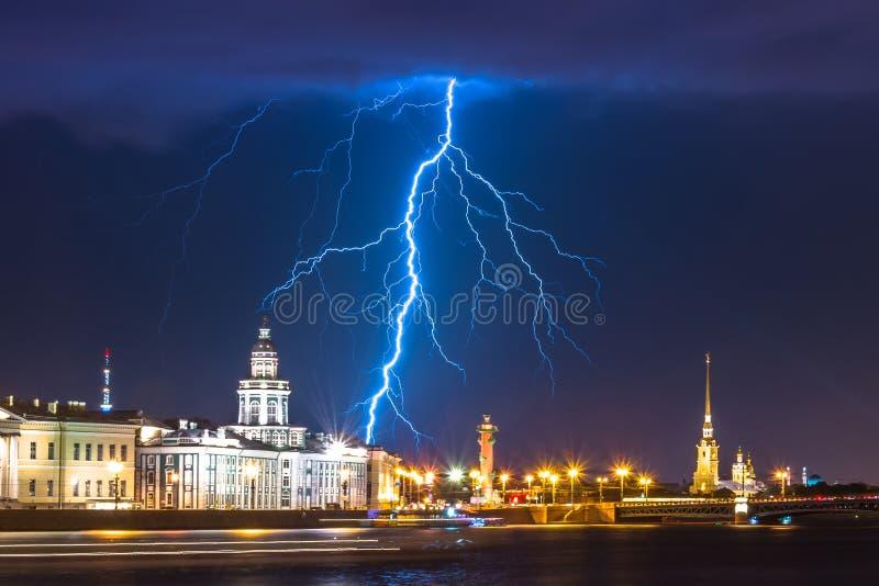 与闪电雷暴闪光的夜在圣彼德堡和Kunstkamera的内娃,彼得和保罗堡垒和有船嘴装饰 免版税图库摄影