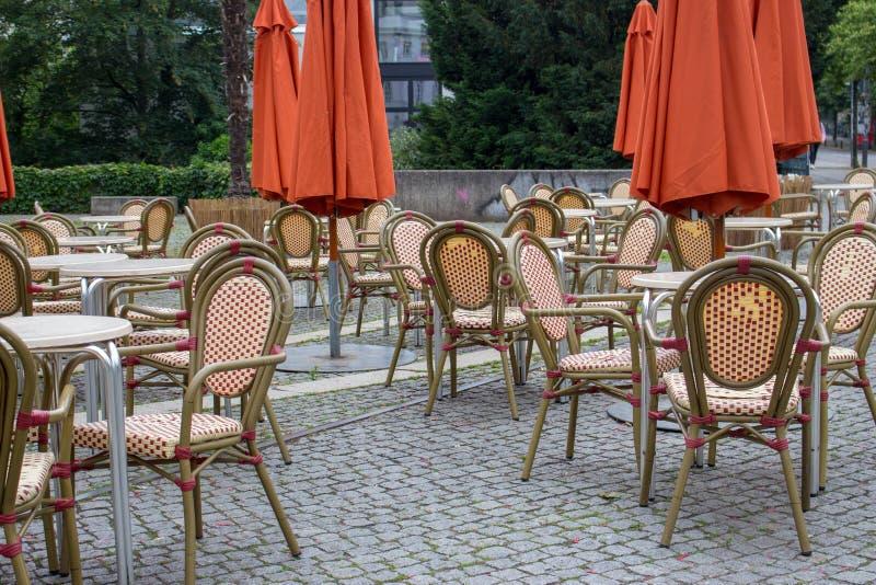 与闭合的伞的空的室外咖啡馆 与空的桌和椅子的街道咖啡馆 餐馆家具概念 免版税图库摄影