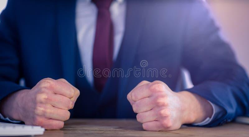 与闭合的拳头的恼怒的商人 免版税库存照片