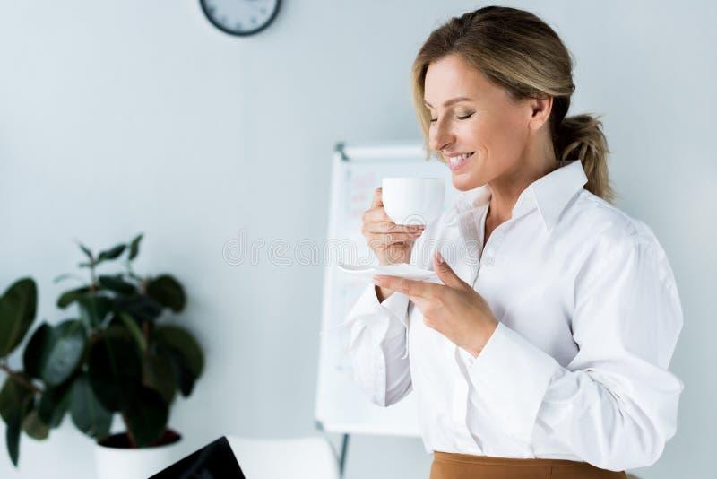 与闭合的眼睛的有吸引力的女实业家嗅咖啡 免版税图库摄影