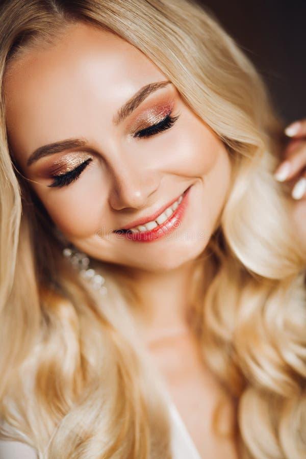 与闭合的眼睛的淫荡微笑的年轻blondie 免版税库存照片