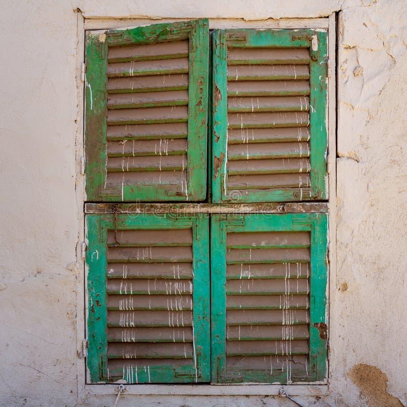 与闭合的绿色快门的老难看的东西窗口在肮脏的砖石墙上 免版税库存图片