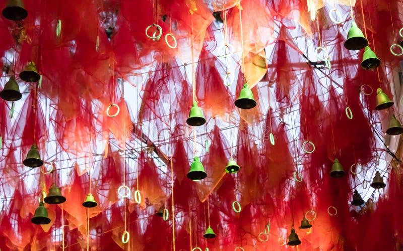 与问候幸运的词的金铃在Kalighat卡利Mandir寺庙加尔各答的红色丝带 香客人愿望和垂悬它  免版税库存照片