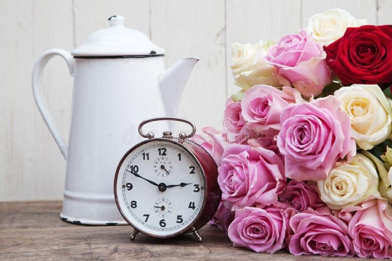 与闹钟和玫瑰的静物画 免版税库存照片