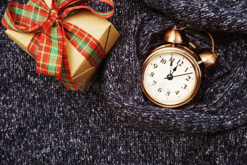 与闹钟和礼物盒的冬天背景在蓝色被编织的布料纹理背景 库存图片