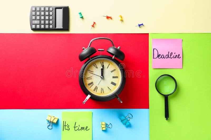 与闹钟的构成和在颜色背景的纸贴纸 r 免版税库存图片