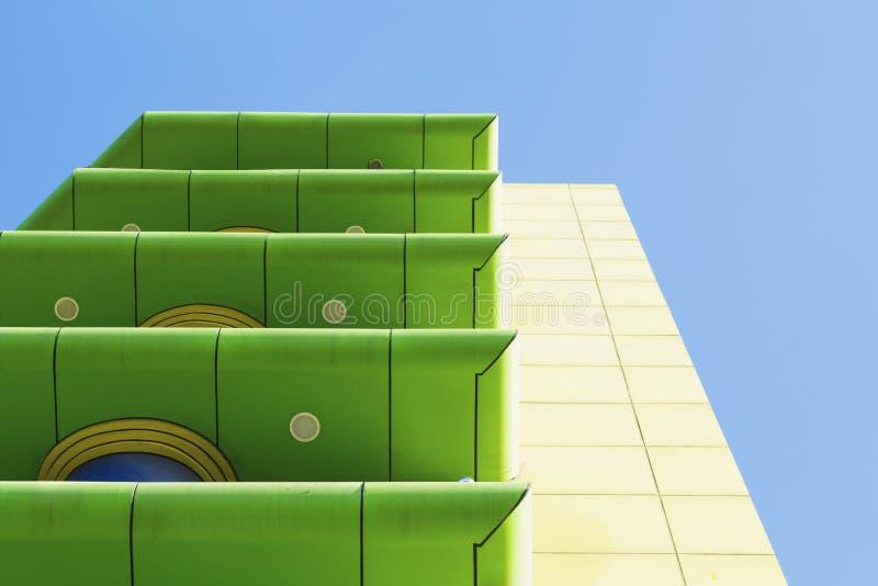 与阳台的现代绿色和黄色大厦蓝天背景的 库存图片
