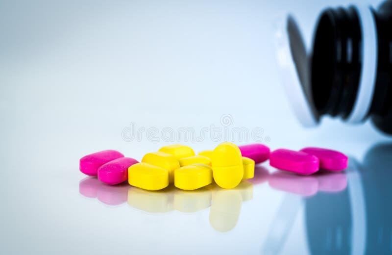 与阴影的黄色和桃红色卵形片剂药片在与被弄脏的药瓶的白色背景 温和减轻痛苦管理 免版税库存照片