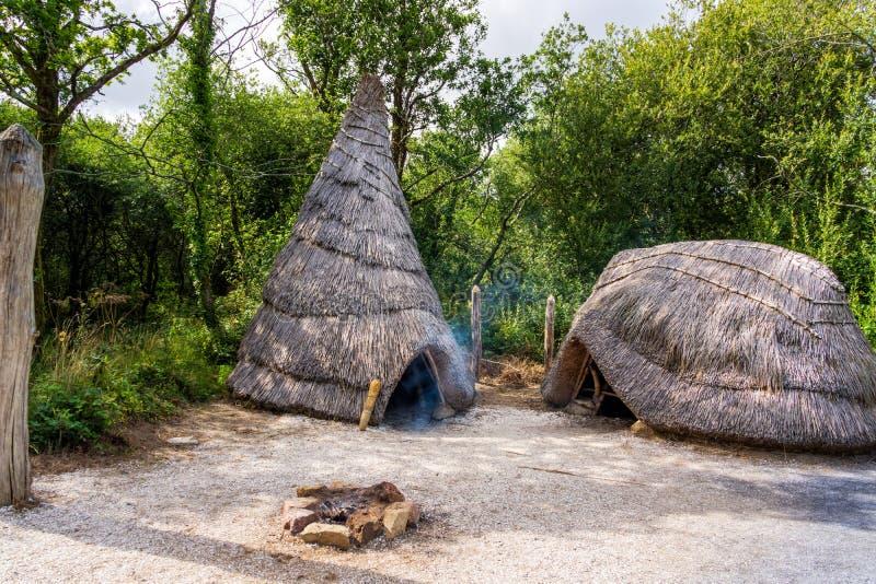 与阵营火,童年年龄人的解决的概念的老茅草屋顶村庄 库存照片