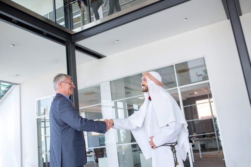 与阿拉伯伙伴的商人握手 免版税库存照片