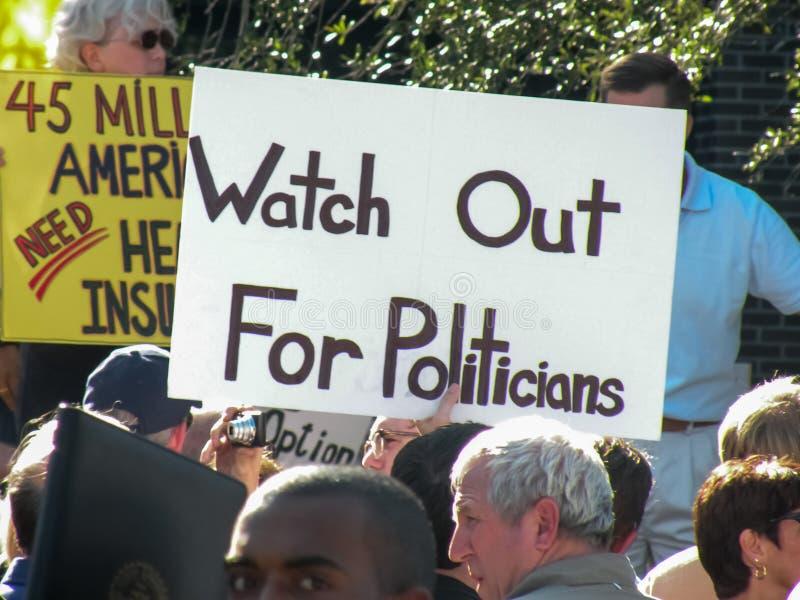 与陈述抗议的标志的政治集会'提防政客' 免版税图库摄影