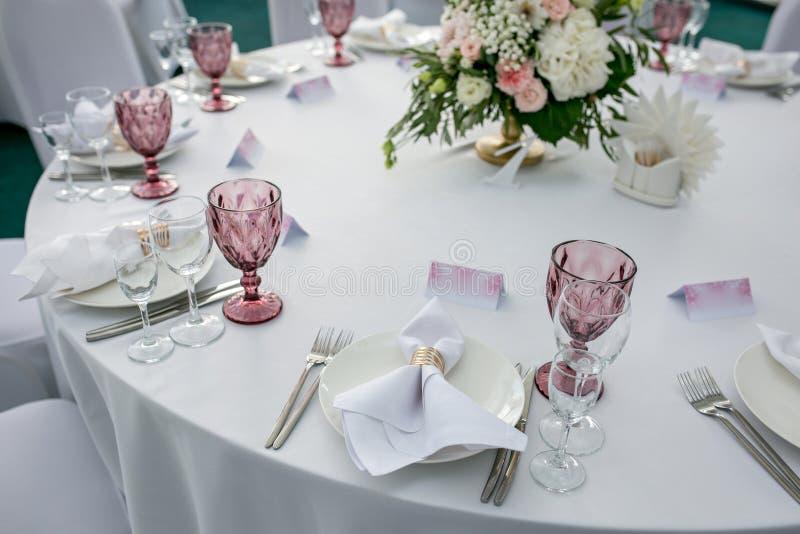 与陶器和花的美好的桌设置党、结婚宴会或者其他欢乐事件的 玻璃器皿和利器为 免版税图库摄影