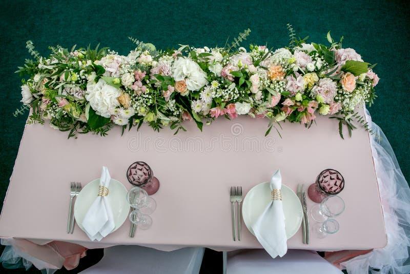 与陶器和长的花forarrangement的美好的桌设置党、结婚宴会或者其他欢乐事件 玻璃器皿 库存照片