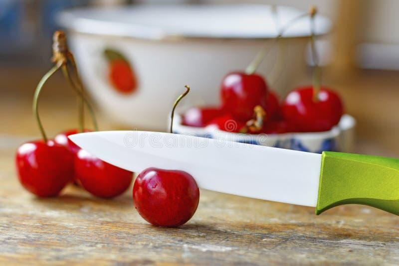与陶瓷刀子的甜红色樱桃在一张老木桌上 免版税图库摄影