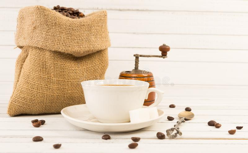 与陶瓷杯子、黄麻袋子和研磨机的新咖啡概念 库存图片